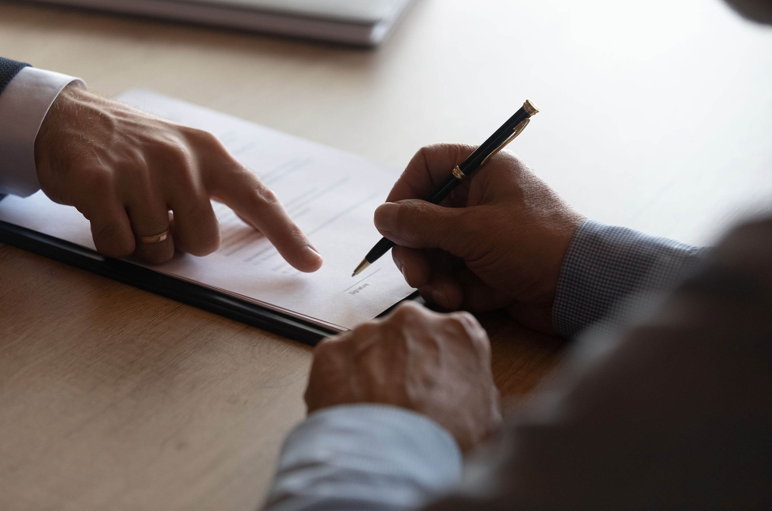 Hands of lawyer pointing at paper for businessman signing contract. Solicitor, legal advisor helping mature client to fill up document, medical insurance form, will, affixing signature. Paperwork